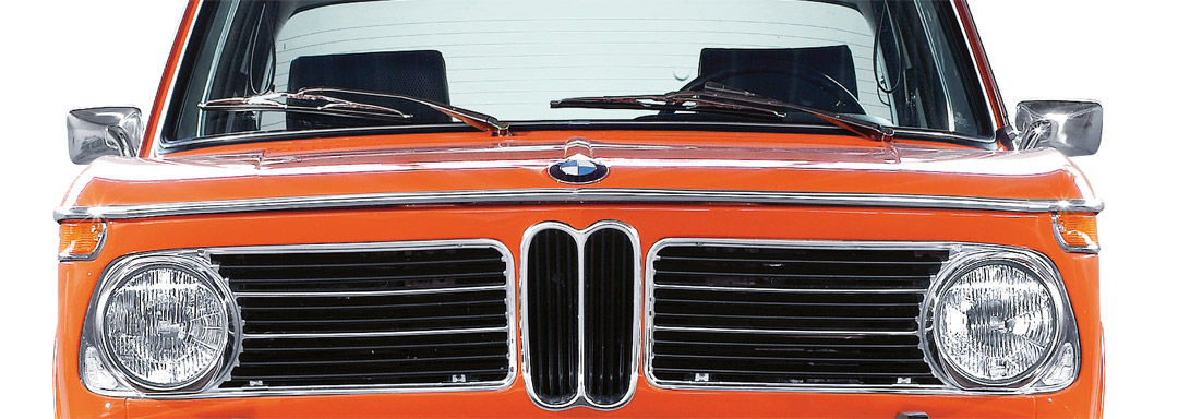 BMW Certified Classic Centers. Close-up of the front end of a classic orange BMW 2002 photographed in-studio on a white background.