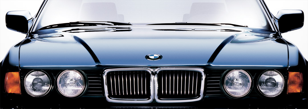 BMW Certified Classic Centers. Close-up of the front end of a classic dark blue BMW 750iL photographed in-studio on a white background.